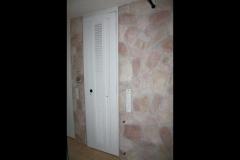 Tür zum Gäste-WC in Mauerstärke. In der Tür befindet sich ein kleiner Schrank für Kleinzeug und Schuhe