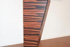 Einseitig schräges Highboard mit Schubkästen auf Gehrung gearbeitet. Vorderstücke mit eingefrästen Griffmulden. Holzart: Makasar Echtholz
