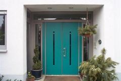 Doppelflüglige Haustür, Rahmen grau lasiert, Türblätter Türkis lackiert. Glasstreifen Kobaltblau